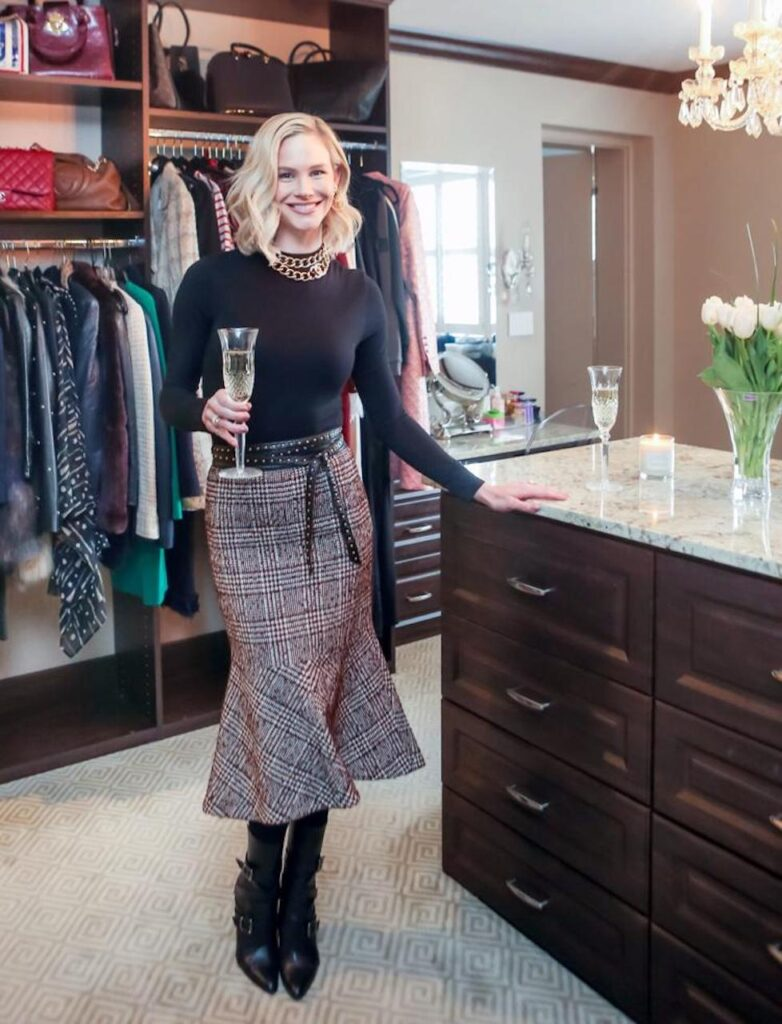 Meghan King standing in a Saint Louis Closet Co. closet with a glass of champagne
